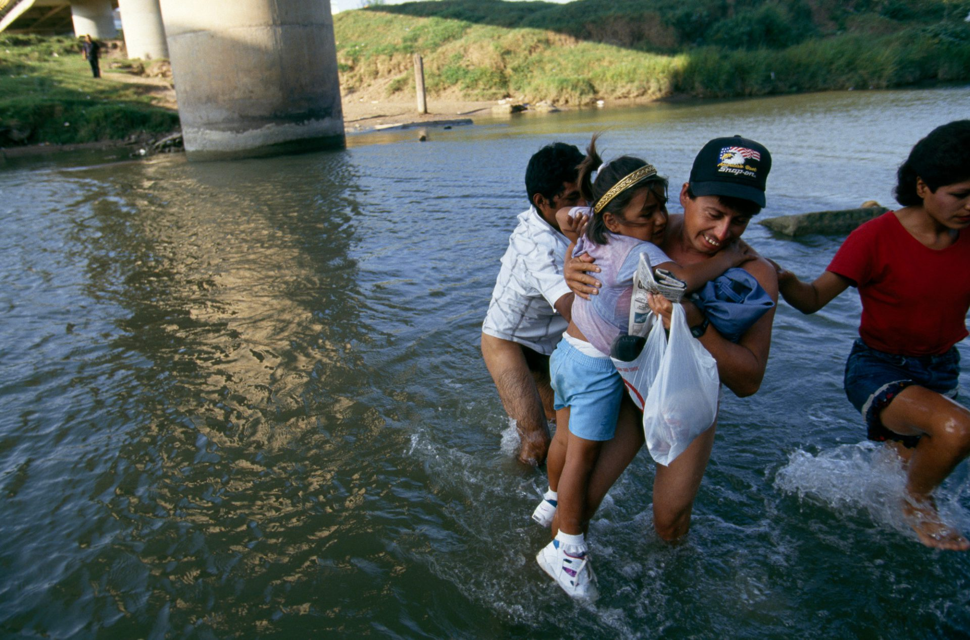 Photo: A Mexican family wade across the Rio Grande beneath the International bridge, leaving Matamoros and entering Brownsville, Texas illegally.