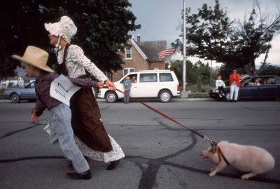 """Photo: Two young contestants in the Mount Pleasant, Utah Pioneer's Pageant struggle with an aspiring """"animal actor."""""""
