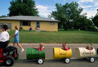 "Photo: Children ride in a parade as part of the ""Middle of Nowhere"" Festival in Ainsworth, Nebraska."