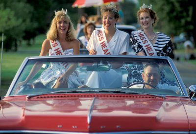 Photo: Contestants from the Miss Heartland beauty pageant are driven in a parade in the Harper County Fair in Harper, Kansas.