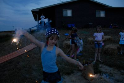 Photo: Ellen Sartore plays with sparklers at a Fourth of July celebration in Greenleaf, KS.