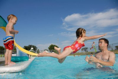 Photo: A man plays with his young children at the public pool in Greenleaf, KS.