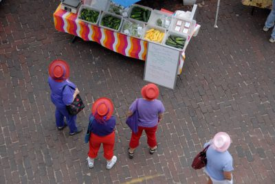 Photo: Three women in red hats shop at the Farmer's market in Lincoln's historic Haymarket district.