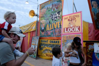 Photo: A woman shows a snake to fair-goers in front of a show at the Nebraska State Fair.