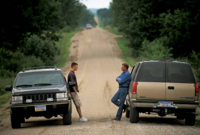 Photo: A father and son relax and talk alongside a gravel road.