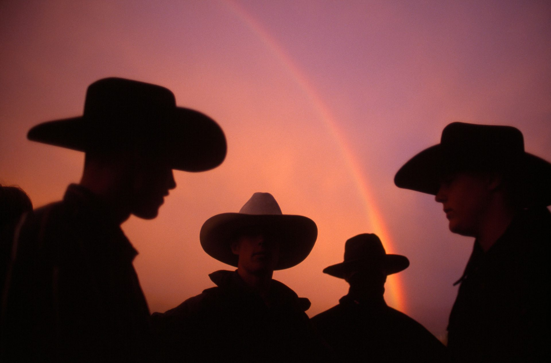 Photo: Cowboys standing in front of a rainbow in Utah.