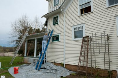 Photo: A woman works to repair a farm house in Nebraska.
