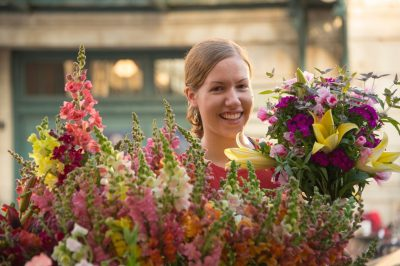 Photo: A woman carries flowers at the Farmer's Market in the historic Haymarket district of Lincoln, Nebraska.