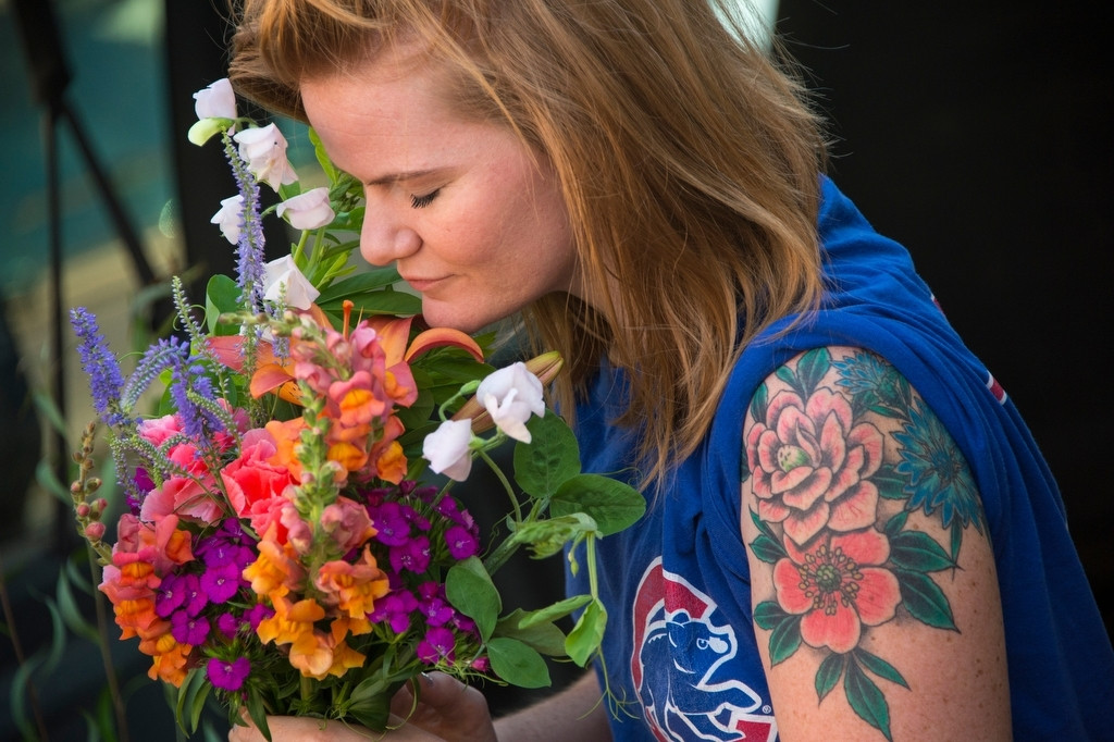 Photo: A woman smells flowers at the Farmer's Market in the historic Haymarket district of Lincoln, Nebraska.
