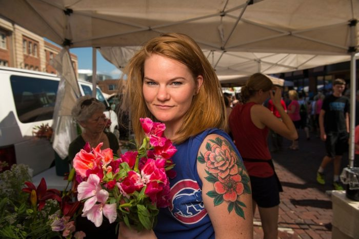Photo: A woman with a floral tattoo poses with the flowers she purchased from the Farmer's Market in the historic Haymarket district of Lincoln, Nebraska.