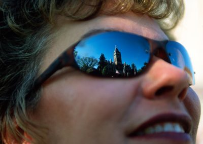 Photo: A woman smiles with the Geneva courthouse reflected in her sunglasses.