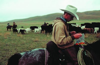 Photo: A rancher's son eats his gummi worms on the go during cattle round up in the Nebraska Sandhills.