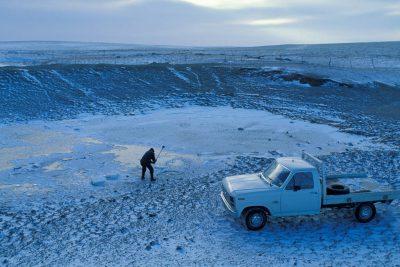 Photo: A rancher breaks open a cattle pond on a ten below day near Wild Horse, CO.