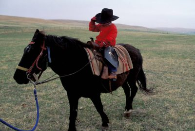 Photo: A young Nebraska boy goes for a ride on a horse at a ranch in the Sandhills.