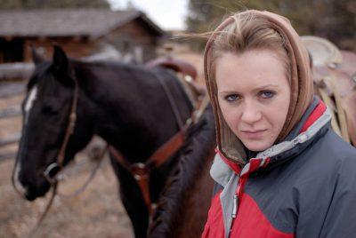Photo: Rachel Cox poses with her horse in the Nebraska Sandhills.