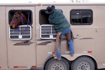 Photo: Tyson Cox climbs on a horse trailer in the Nebraska Sandhills.