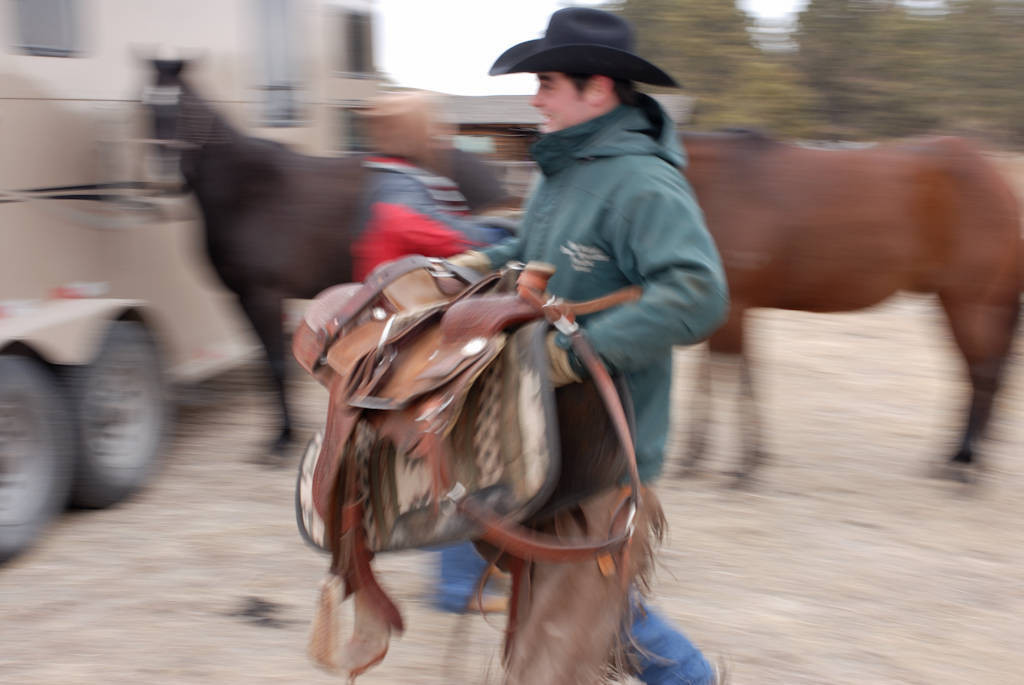 Photo: Tyson Cox carries a saddle in the Nebraska Sandhills.