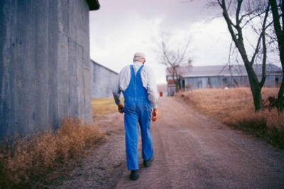 Photo: A Nebraska farmer makes his way past an outbuilding on a dirt road.