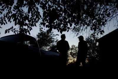 Photo: Two farmers are silhouetted against the setting sun.