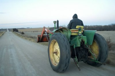 Photo: A farmer drives a tractor down a gravel road in Elmwood, Nebraska.