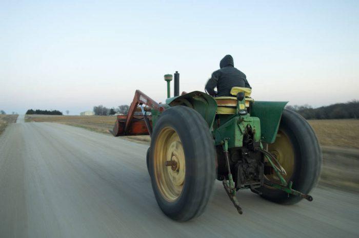 Photo: A farmer drives a tractor down a gravel road in Elmwood, Nebraska.