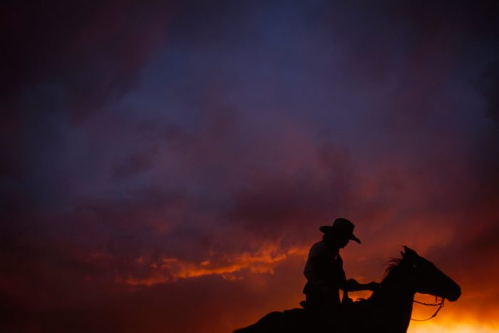 Photo: A cowboy is silhouetted against a colorful sky after a storm