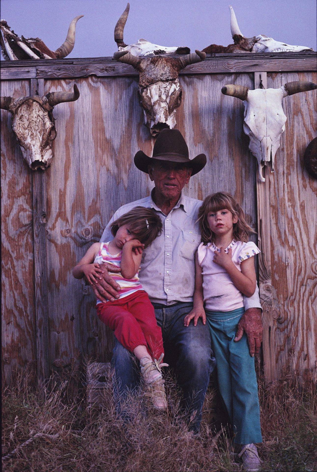 Photo: A grandfather poses with his granddaughters at his cattle ranch at the edge of the Mojave desert near Goffs, California.