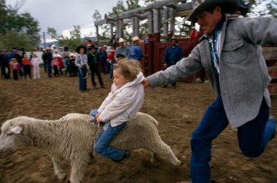 "Photo: A child is helped ride a sheep during the ""mutton busting"" event at the annual rodeo in Leadore, Idaho."