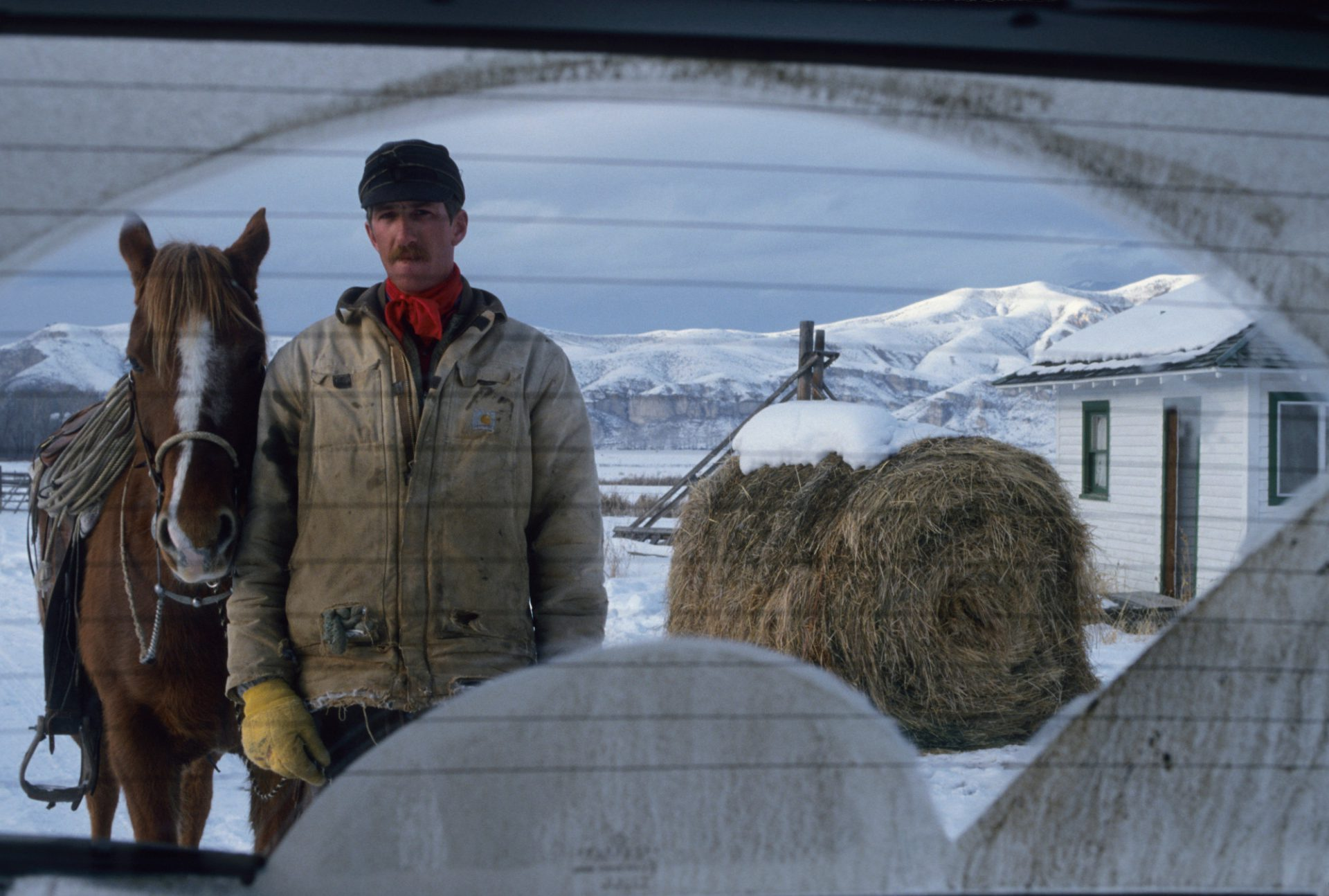 Photo: Portrait of a cattleman through a windshield standing with his horse on Hot Spings ranch north of Salmon, Idaho.