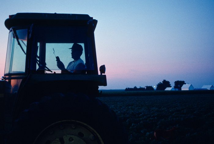 Photo: A farmer dials his cell phone from the cab of his tractor in rural Flatville, IL.