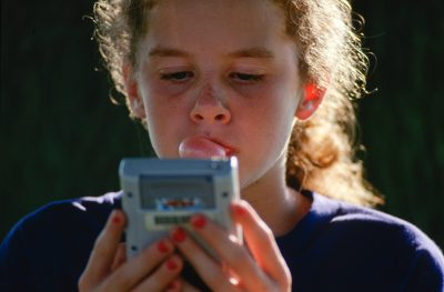 Photo: A girl chews bubble gum and uses a portable gaming device in rural Flatville, IL.