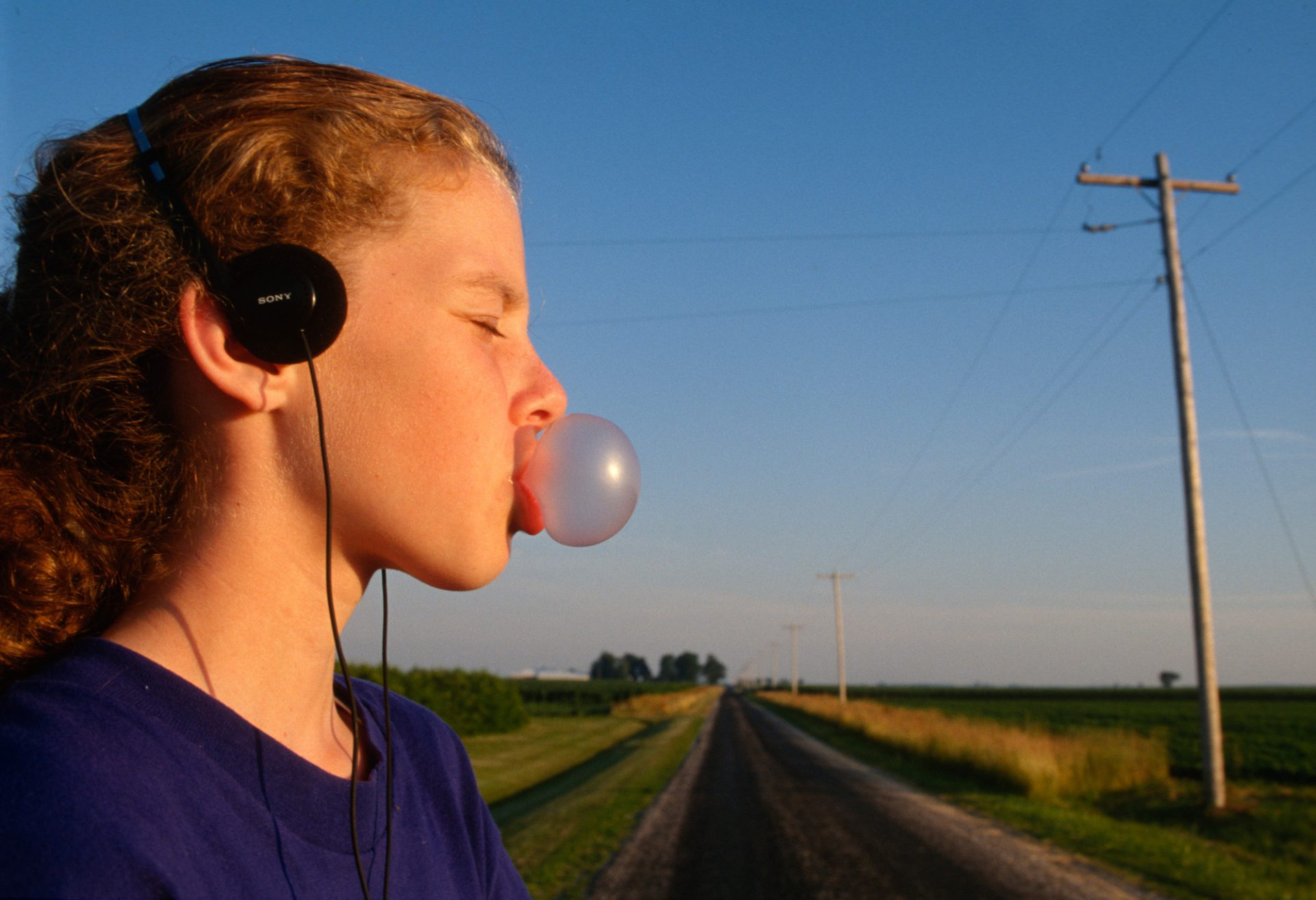 Photo: A girl chews bubble gum and listens to music in rural Flatville, IL.