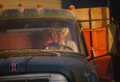 Photo: A man sits in his truck by grain elevators.