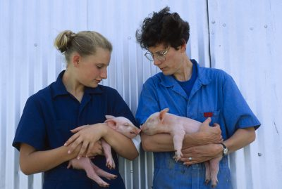Photo: A mother and daughter hold piglets, Bennet, Nebraska.