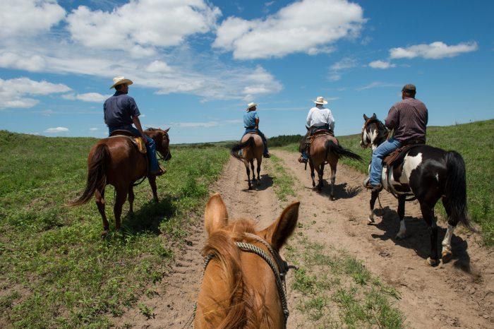 Photo: Ranchers on horseback follow a dirt road.
