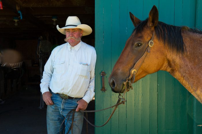 Photo: A rancher leans in the doorway of a barn with his horse.