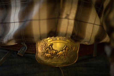 Photo: A detail shot of a man's belt buckle.