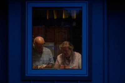 Photo: A man and a woman, as seen through their kitchen window.