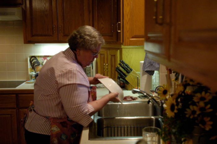 Photo: Sharon Sartore does the supper dishes at her home in Elkhorn, NE.