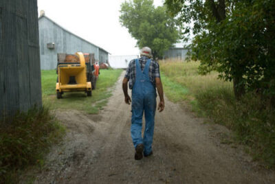 Photo: An old man walks down a dirt road on a farm.