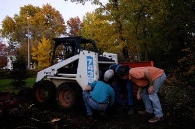Photo: Three men examine a broken excavating machine in Nebraska.