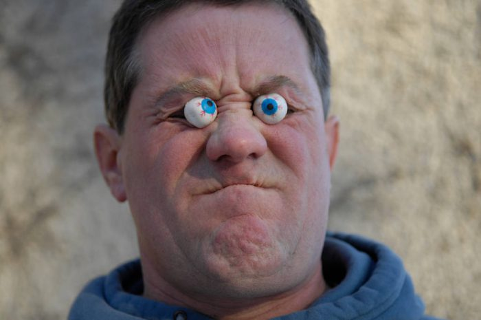 Photo: A man looks frustrated wearing fake googly eyes.
