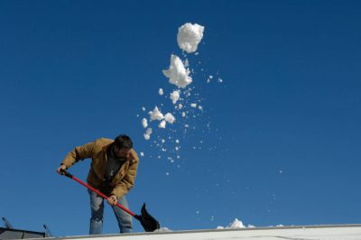 Photo: A man shovels snow off off a roof after a snowstorm.