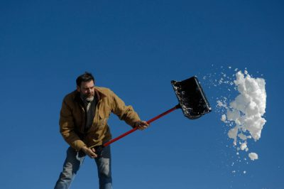 Photo: A man shovels snow off off a roof after a snowstorm.