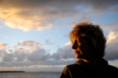 Photo: A woman looks out into scenic Leech Lake at sunset in Minnesota.