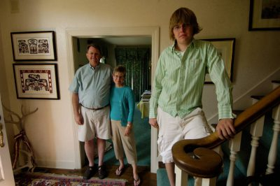 Photo: A high school graduate poses with his parents in their home.