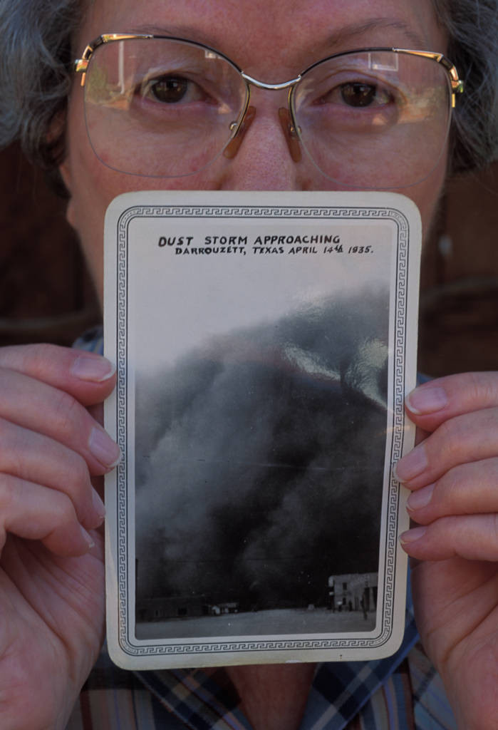 Photo: Faynell Meese holds up a photo of a dust storm rolling into Darrouzet, Texas.