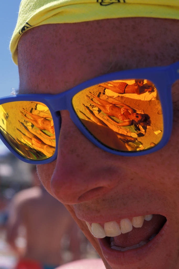 Photo: A male student on spring break smiles in excitement as he stares at bikini clad women that are reflected in his sunglasses.
