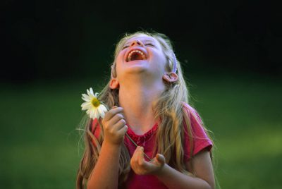 Photo: A girl plays with a daisy and laughs in Lincoln, Nebraska.