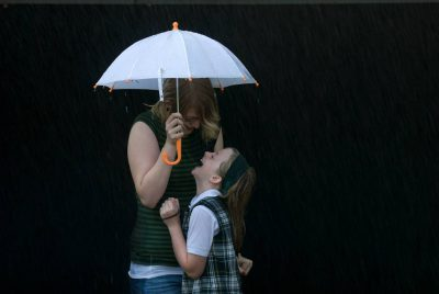 "Photo: A woman and a girl cram themselves under a tiny umbrella to avoid ""rain"" from a garden hose in Lincoln, Nebraska."